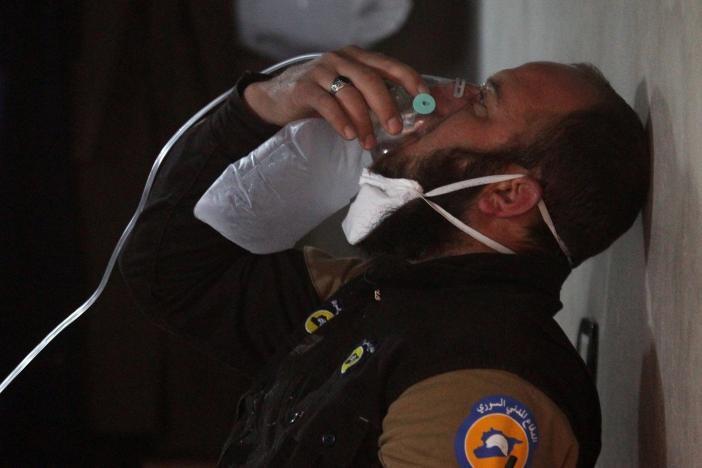圖為一名民防組織人員戴著氧氣罩的畫面。路透