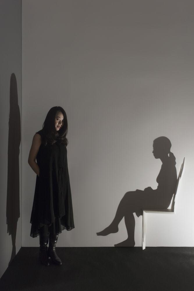 山下工美「光影」系列作品,女人坐在用木材形塑的椅子,在昏暗的光線下,彷彿若有所思...
