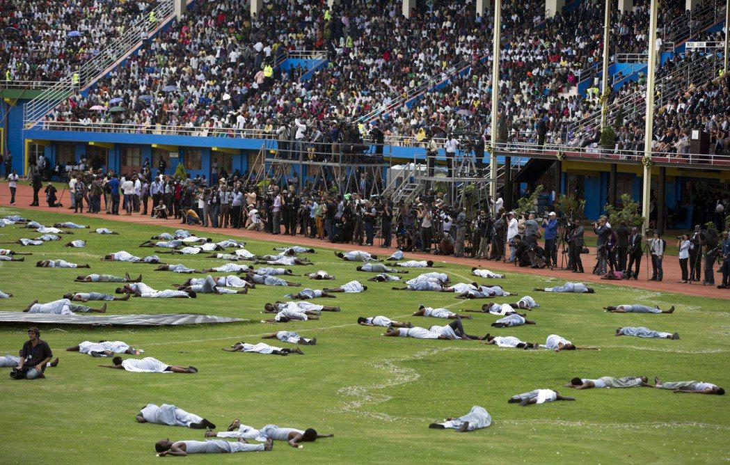 盧安達阿馬胡羅體育場舉行大屠殺反思日的紀念活動,許多參與者橫躺在體育場內悲傷哭泣...