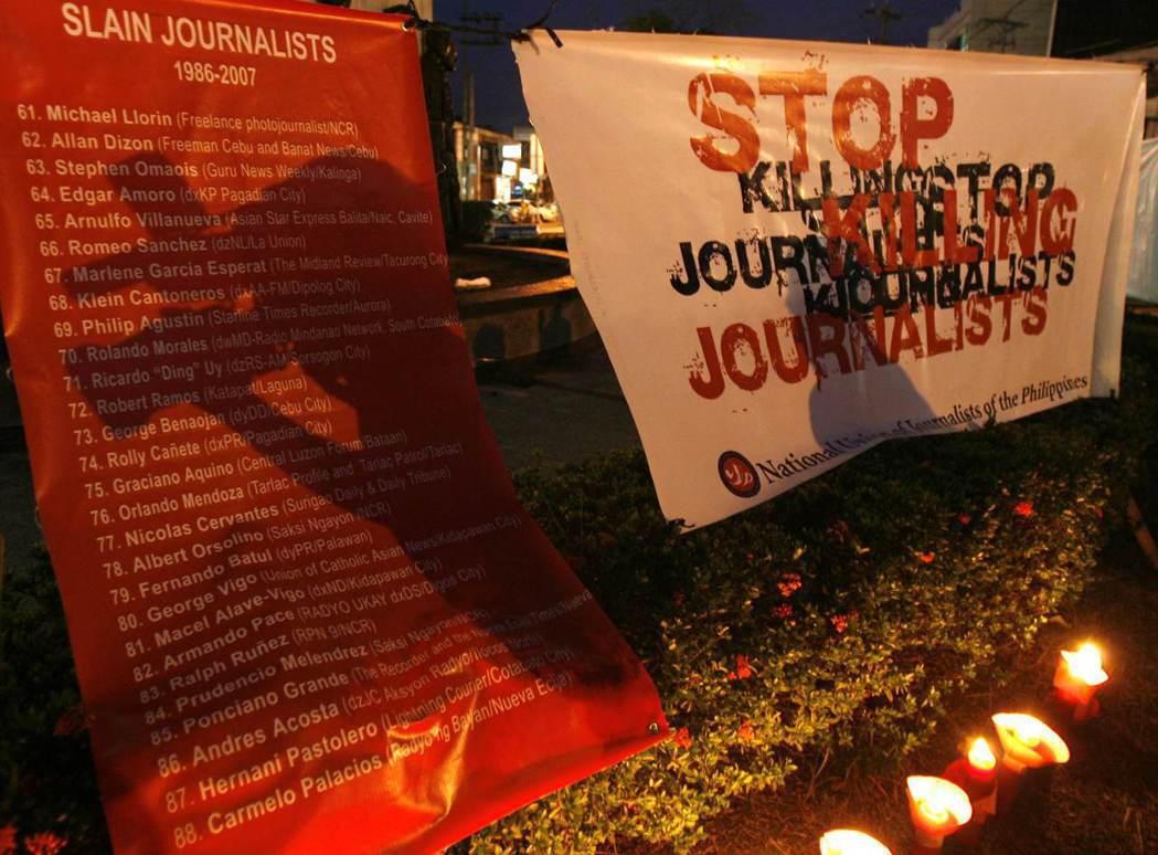 圖為2007年在馬尼拉舉行的世界新聞自由日禱告會,攝影師的影子倒映在菲律賓被殺的...