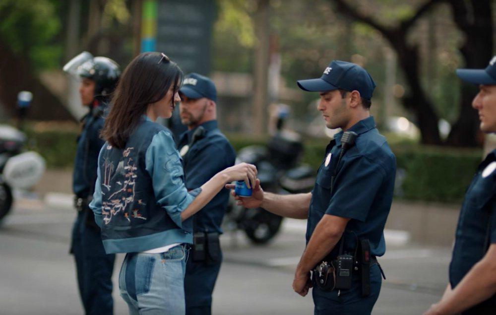 百事可樂廣告中,新生代超模坎達兒.珍娜(左)拿了一罐百事可樂給警察,化解了示威衝...