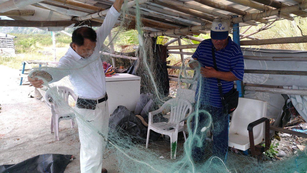 漁民張慶來(右)及為救援海龜所割破的漁網。圖/林務局提供