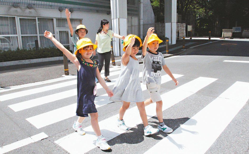 小學生過馬路,以舉手向駕駛人示意效果很好;小學生帽子上都別著小心學童的標誌。...