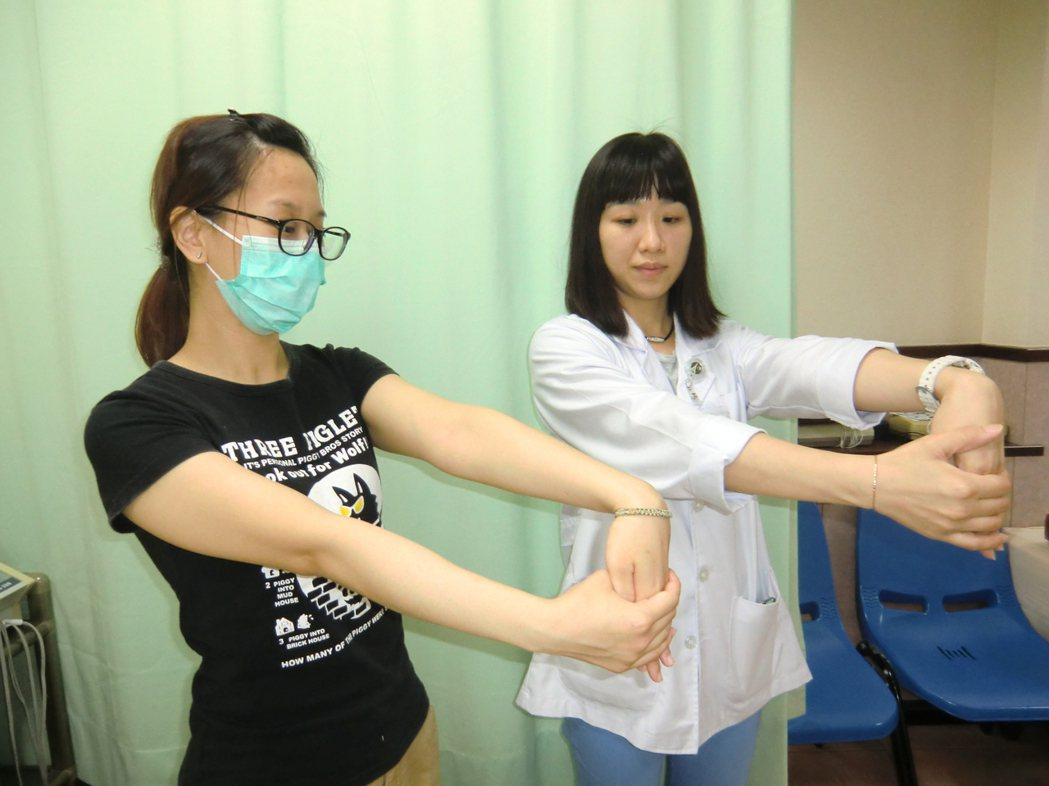 第三式:一手手掌朝下,另一手將其手背,往下壓且手臂伸直。記者謝梅芬/攝影