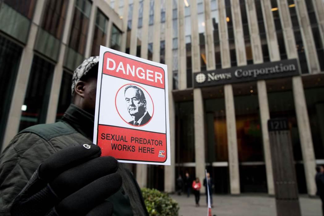 1名示威者19日在福斯新聞網的紐約總部前,高舉一張歐萊利的海報,稱他是危險人物。...