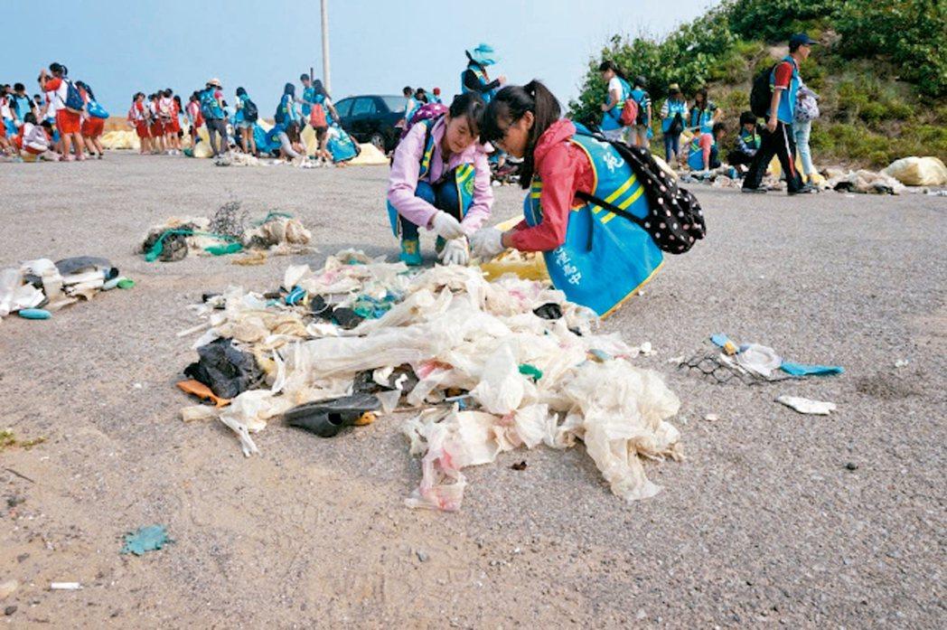 海洋廢棄物數量第一名是塑膠袋,圖為淨灘活動,清出大量垃圾,其中以塑膠袋最多。 報...