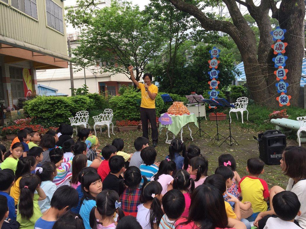 淡水忠山國小在校園為一棵九十歲樟樹的舉辦慶生活動,小朋友吹奏陶笛,用小卡片寫下要...