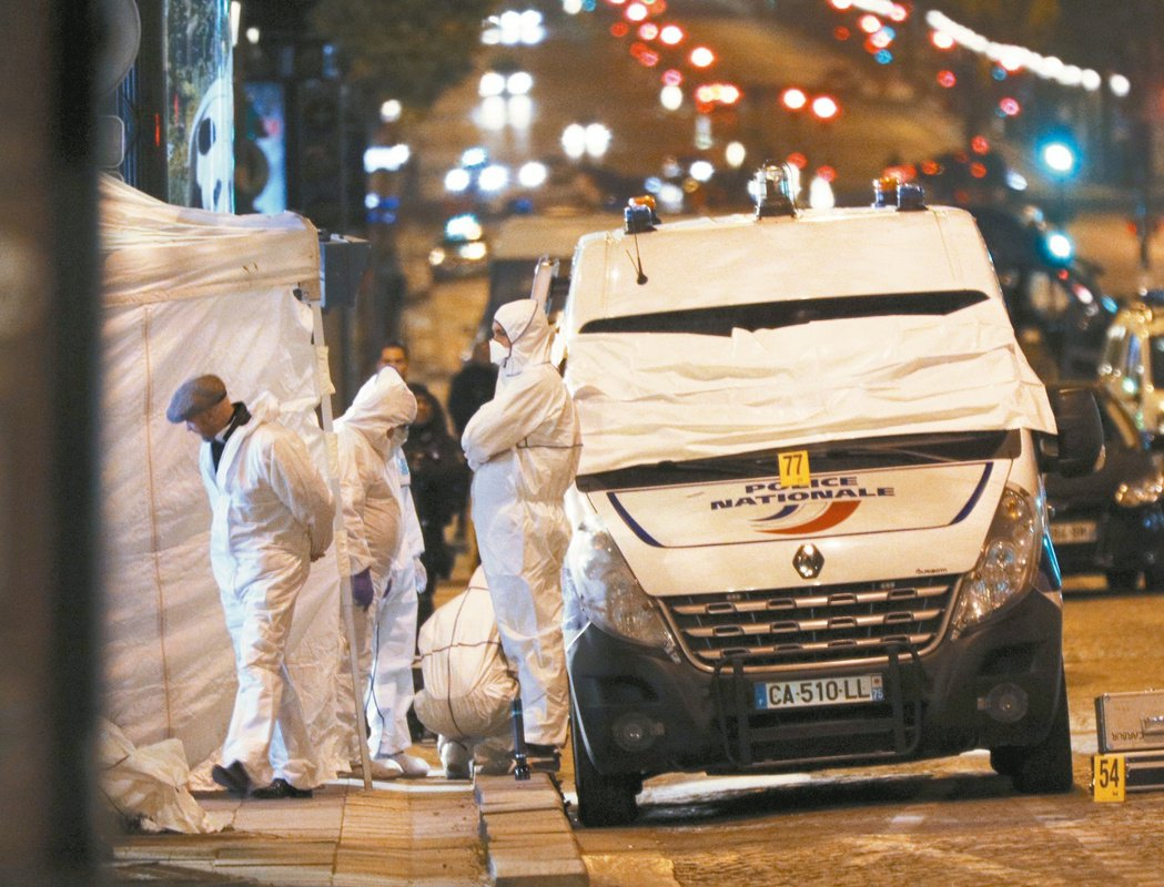 巴黎香榭麗舍大道昨晚發生恐怖攻擊,鑑識人員在遭到槍擊的警用廂型車附近蒐證。(歐新...