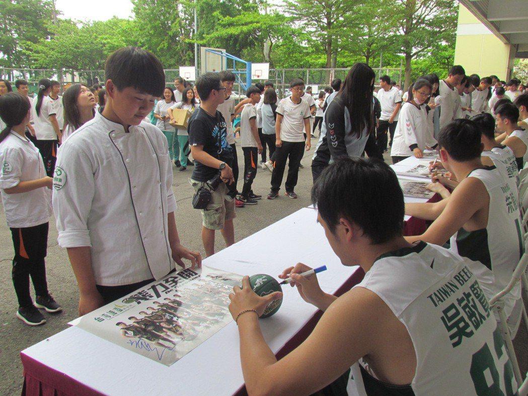 「拜託在我的球上面簽名!」同德家商學生拿出海報、衣服或筆記本,給台啤職籃的球員簽...