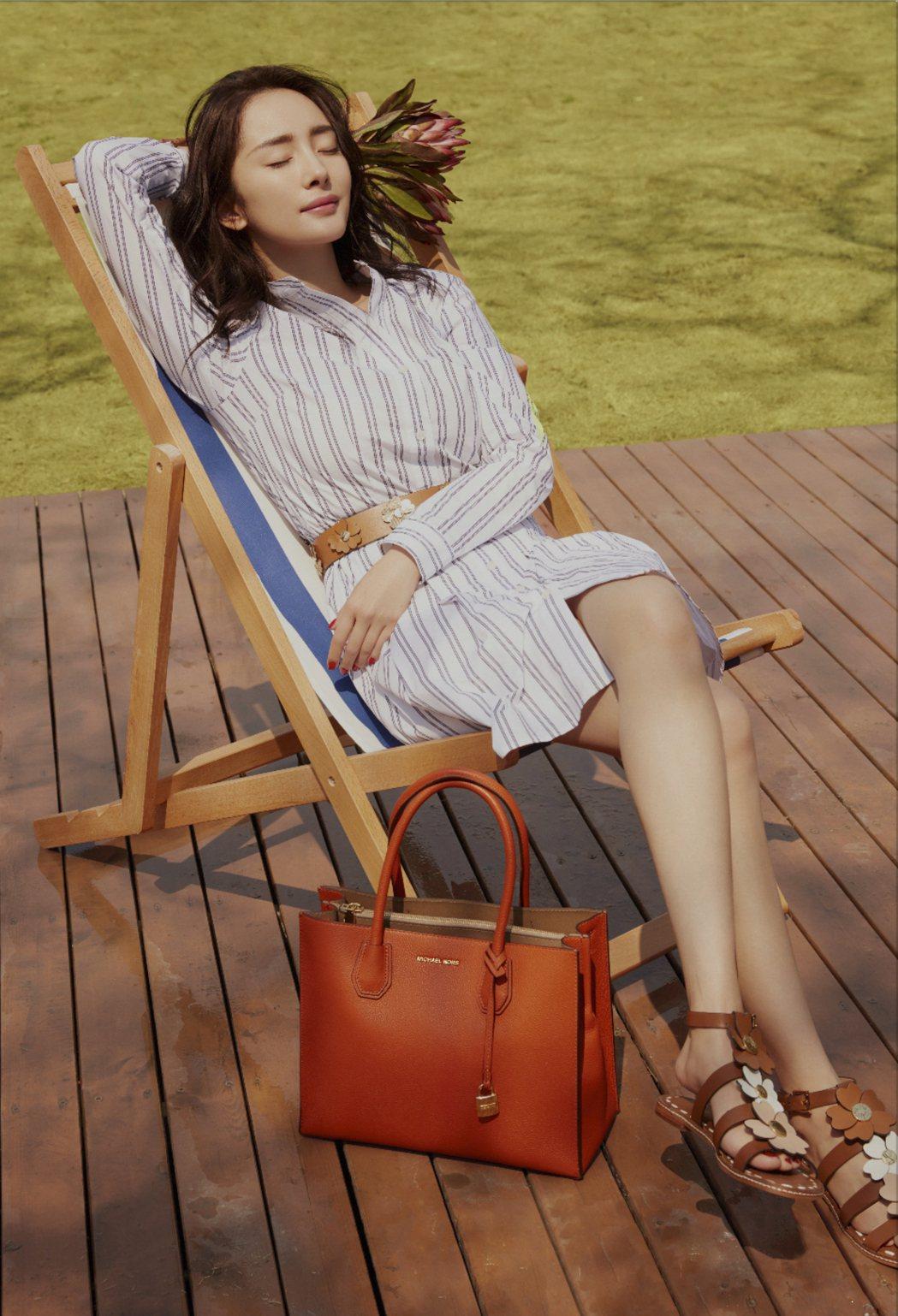 楊冪以條紋長板襯衫裙搭襯澄橘色包款,有舒心的視覺。圖/MICHAEL KORS提