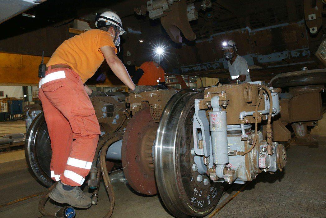 台灣高鐵首度公開高鐵列車「轉向架檢修」(GI)過程,工程人員在車廂底部裝修轉向架...
