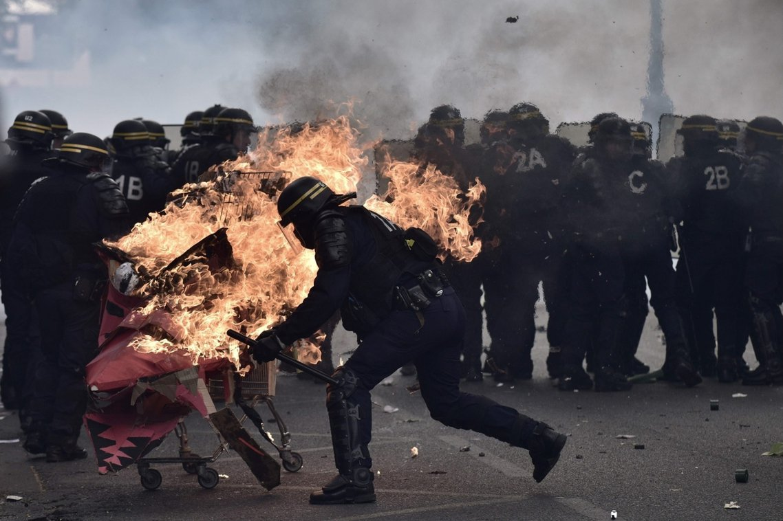 一輛被被汽油彈點燃的推車,正撞向巴黎街頭的鎮暴警察。 圖/法新社