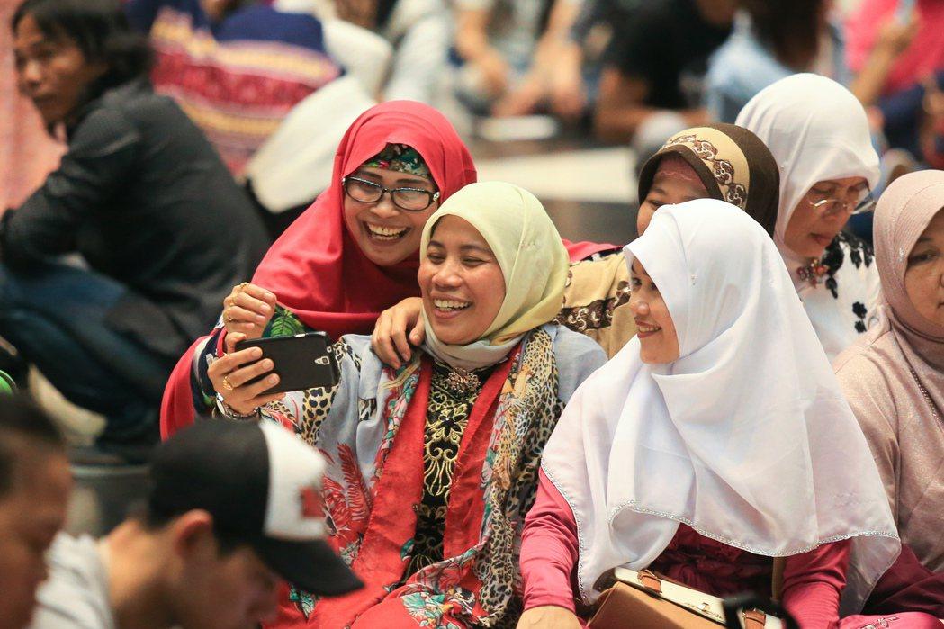 穆斯林移工在台北火車站大廳參與開齋節活動,他們自備食物穿著亮麗的穆斯林傳統服飾,...