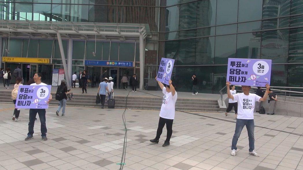 首爾車站正門前,選務人員正高聲督促市民參與投票。 攝影/宣杰