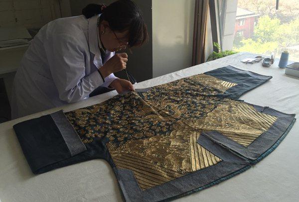 首都博物館修復師正在修復清代盤金繡龍紋上衣。 (新華網)