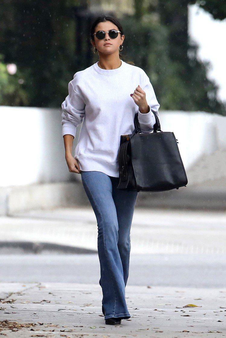 席琳娜戈梅茲以黑色Rogue包款搭配簡單外出服。圖/COACH提供