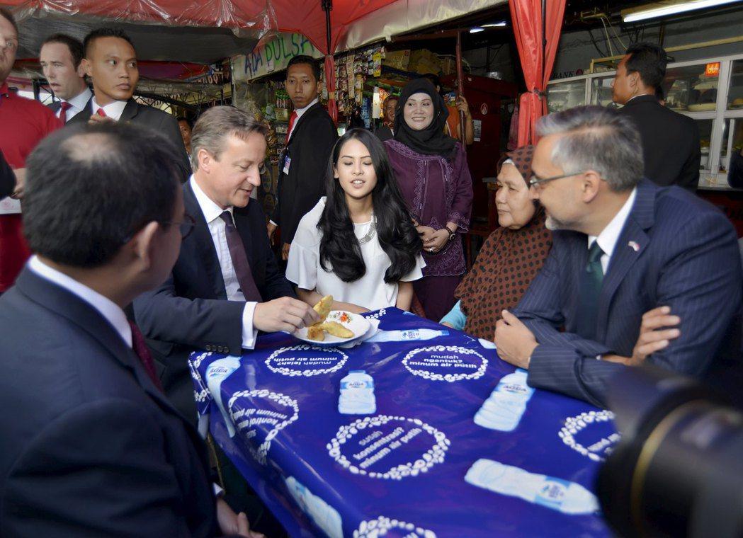 印尼路邊攤小吃盛行,英國前首相卡麥隆(左二)二○一五年訪問雅加達,也曾光顧路邊攤...