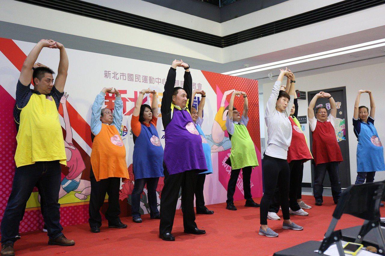 新北市中和國民運動中心今天邀30對準爸爸媽媽一起練習孕婦瑜珈,準爸爸們穿上孕婦體...