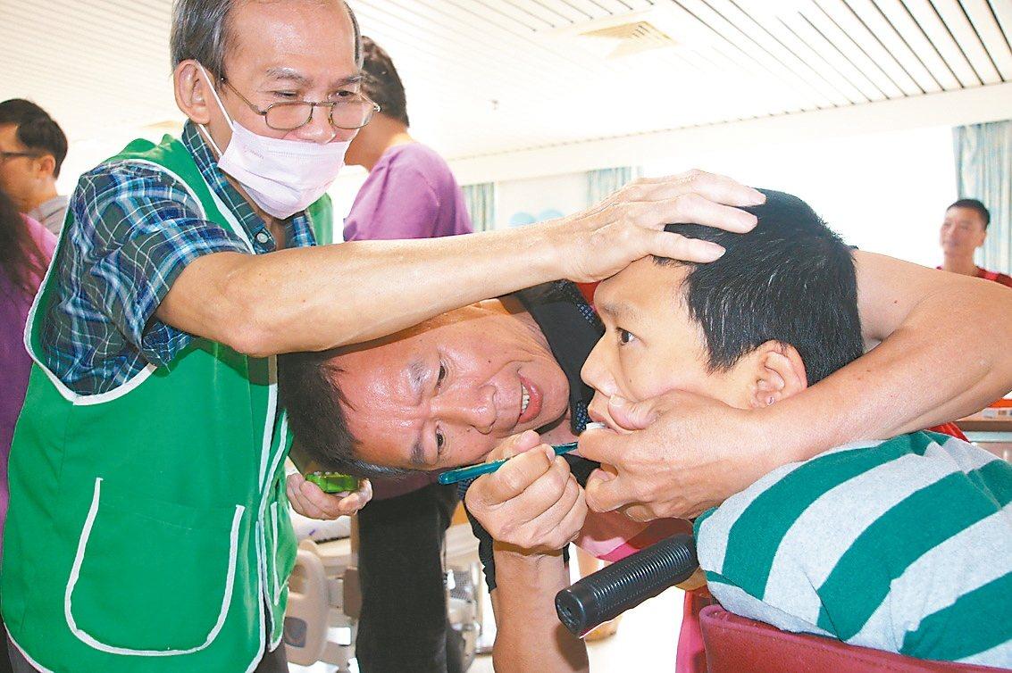 八里愛心教養院辦照顧達人競賽,院生的父親們化身慈母,為孩子刷牙。 記者施鴻基/攝...