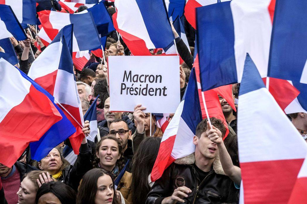 法國民眾7日在巴黎羅浮宮地下商場慶祝馬克宏當選總統。歐新社