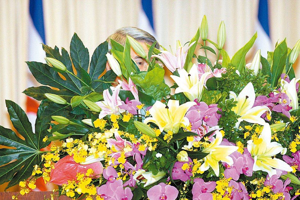 行事低調的新光金董事長吳東進主持股東會,連上台致詞都刻意隱身花叢後,避開媒體的鏡...