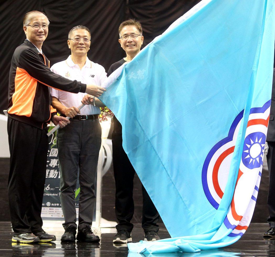 在體育署長林德福(中)見證下,由台大校長楊泮池(左)將會旗交接給下屆主辦學校中央...