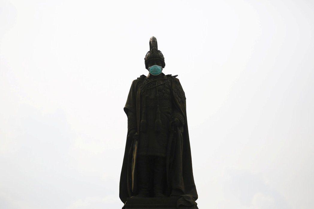加德滿都的空汙日益嚴重,圖為一座被戴上口罩的佛像。 (路透)