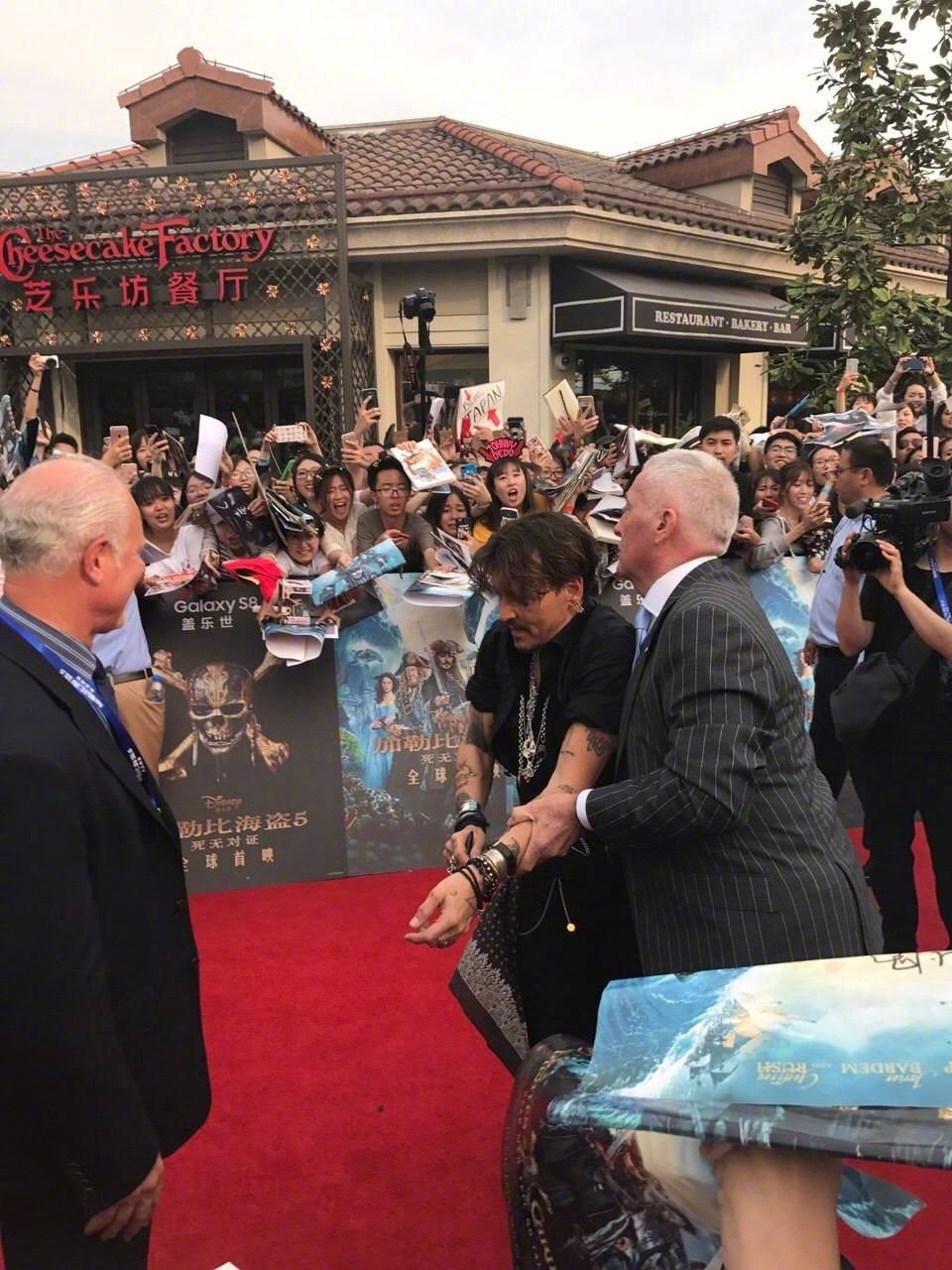保鏢趕著將強尼戴普帶走,強尼戴普卻極力想為粉絲簽名。 圖/擷自微博