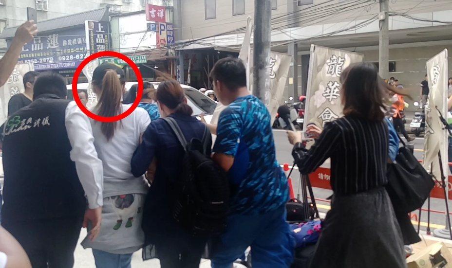 謝金燕(紅圈白衣者)趁亂快閃上車。記者林怡秀/攝影