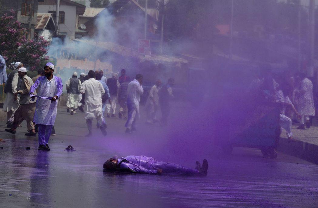 當零星衝突升級:軍警以染成紫色的水柱沖著抗議人群...。 圖/法新社