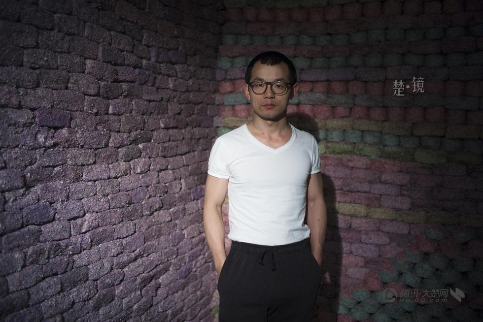 藝術家柯明與他砌的人民幣牆。 (大楚網)