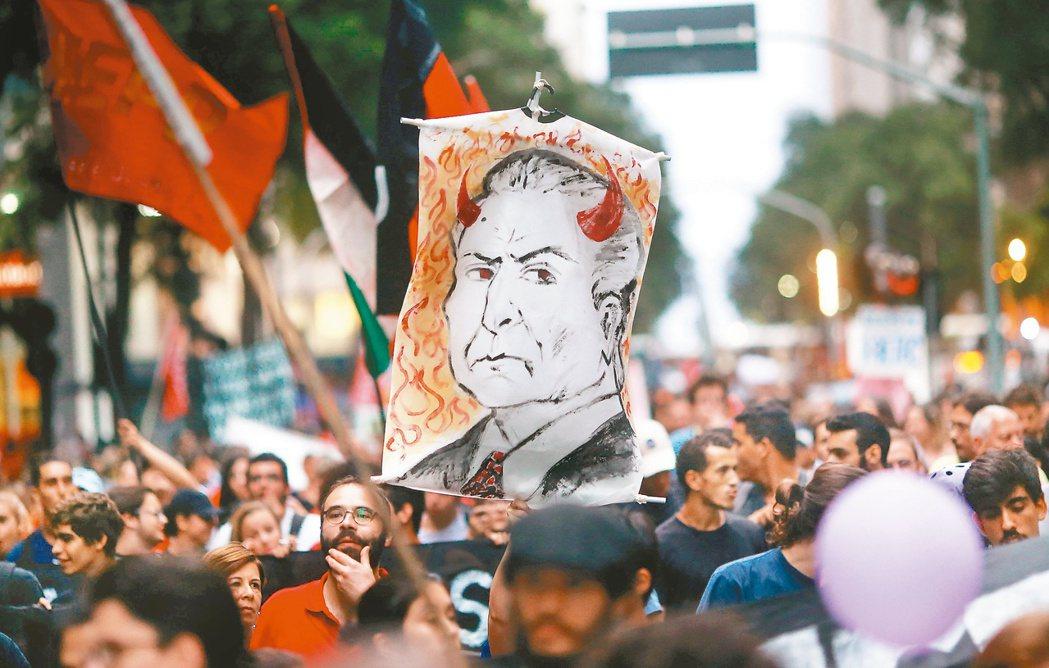 巴西新總統泰梅爾可能遭到彈劾,圖為巴西民眾25日舉泰梅爾畫像抗議。 (路透)