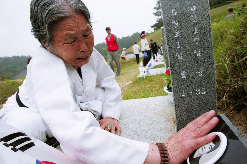 關於過去的記憶,南韓還有很多故事需要交代。圖為一名韓國母親,正在518紀念公墓,...