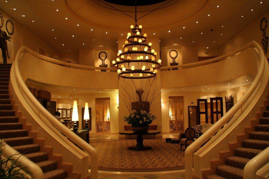 通過綠意庭園和如鏡水池進入Saxon Hotel美麗的挑高門廳,兩座延伸往二樓的...