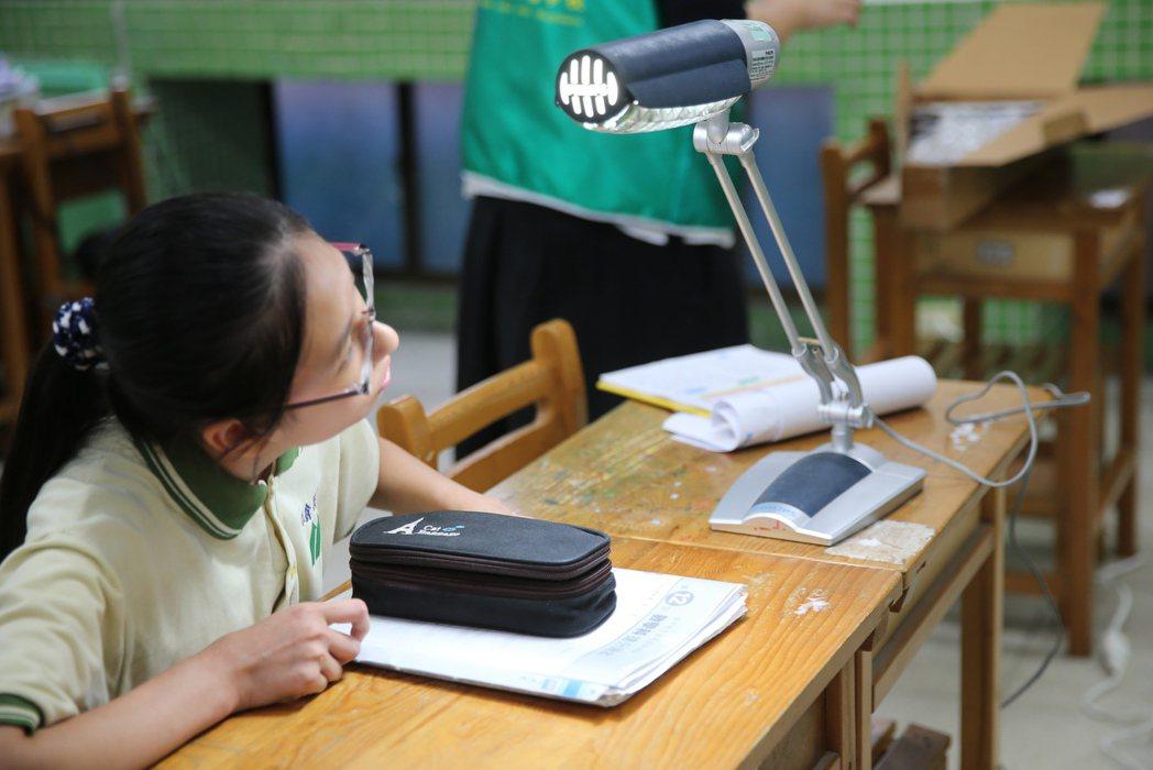 考生要求增加燈光量度,工作人員馬上在考生桌上添加檯燈滿足考生需求。記者徐兆玄/攝...