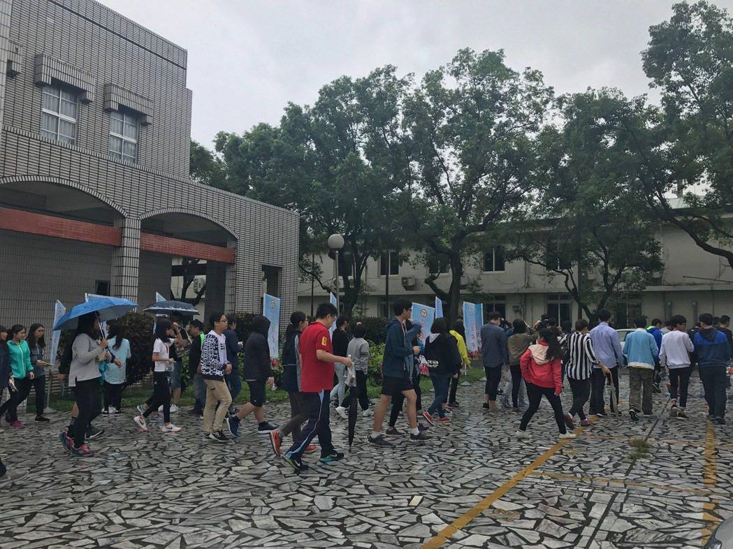 今天天候不佳,有些學生撐傘應試。記者王思慧/攝影