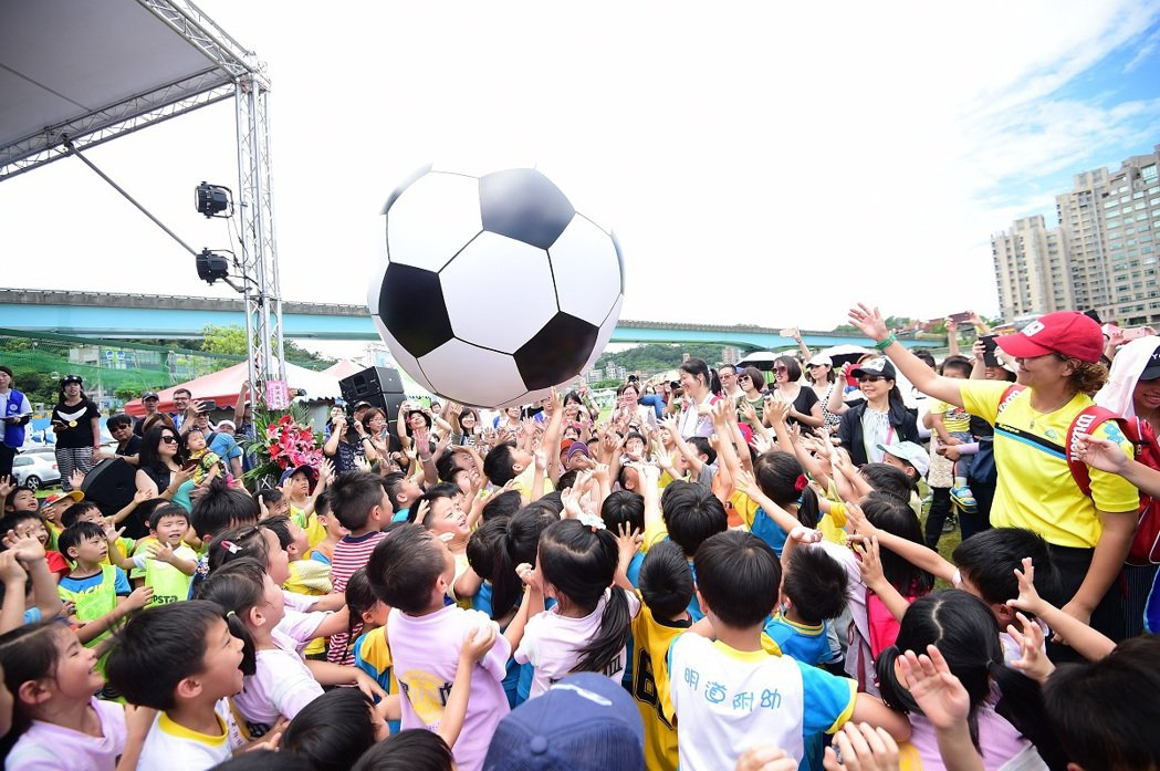 足球小將們高舉雙手滾動巨型足球,象徵著小朋友在場上團結滾動足球的熱情和齊心合力將...