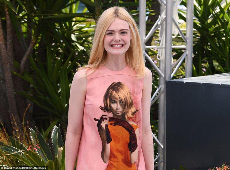 在記者會上艾兒芬妮穿著Prada秋冬系列的A字削肩粉紅色洋裝,上頭印著由Robe...