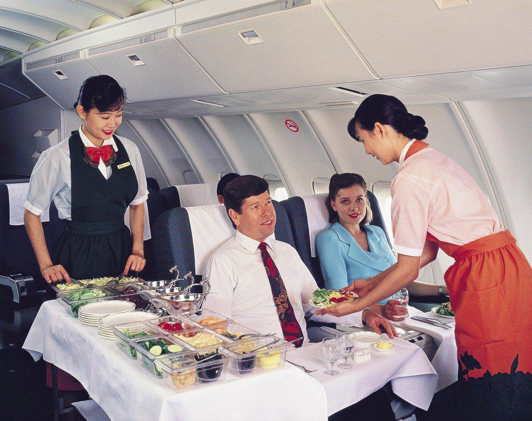 長榮航空空服員穿著第一代制服,在機上提供旅客餐點。 報系資料照