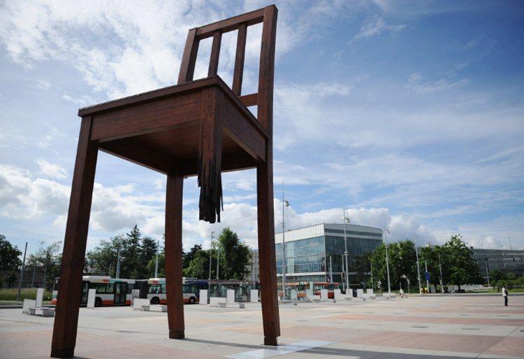 日內瓦聯合國歐洲總部萬國宮前廣場,有一把斷了1隻腳的巨大紅色「三腳椅」塑像,相當...