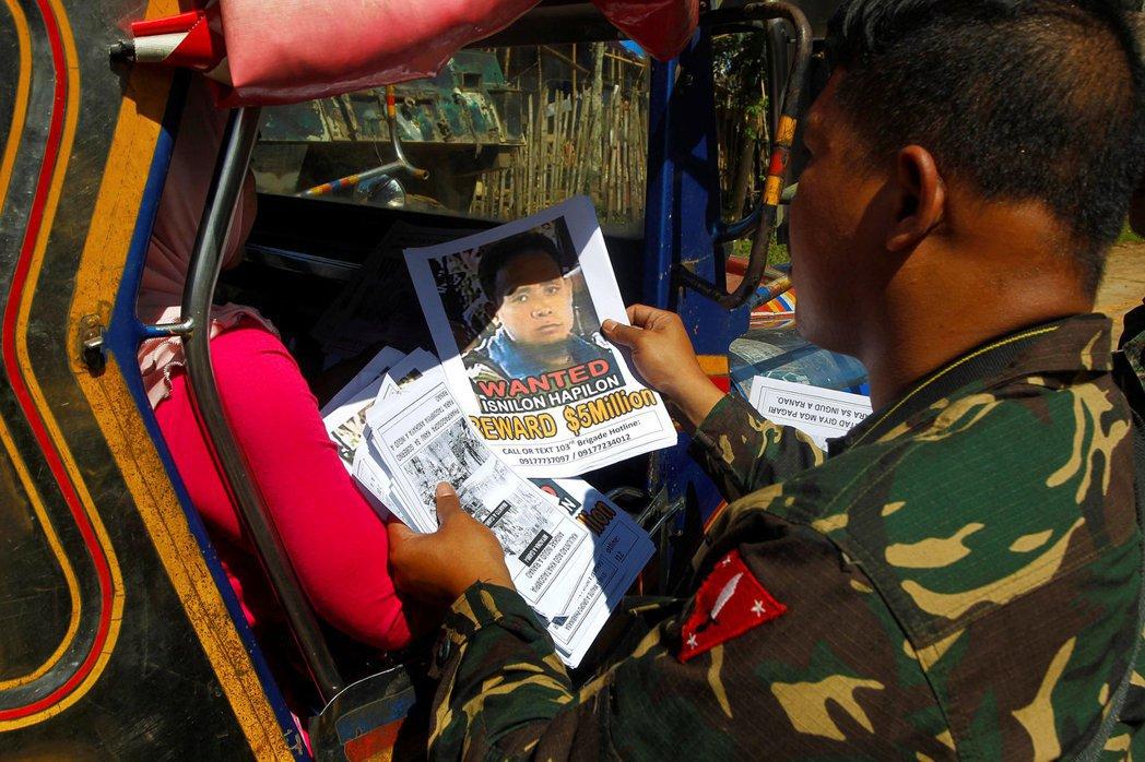 一名士兵正看著哈比倫的懸賞單,哈比倫是被美國政府懸賞500萬美金,希望活捉的高價...