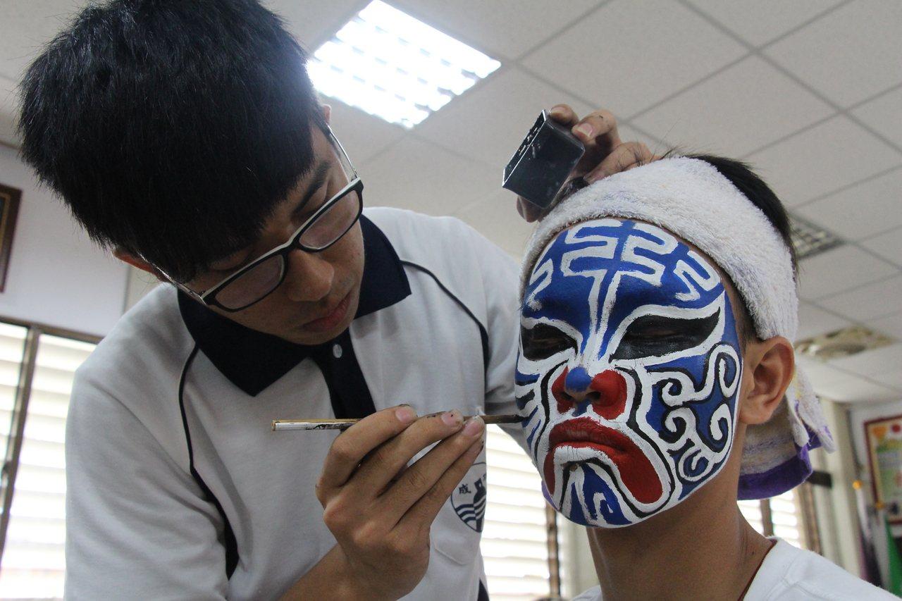 郭勁鴻(左)對畫臉、跳陣、抬轎等各種民俗技藝技巧已十分熟稔。記者李蕙君/攝影