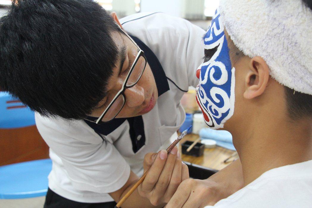 郭勁鴻(左)對畫臉、跳陣、抬轎等各種民俗技藝技巧十分熟稔。記者李蕙君/攝影