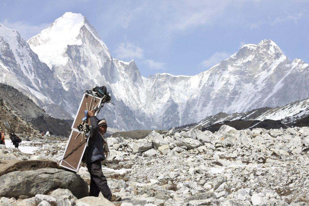 珠峰山區一名背工背負的箱子裡裝有氧氣筒。 (美聯社)
