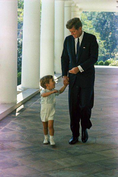 1963年10月10日,甘迺迪牽著兒子小約翰走在白宮長廊。一個半月後甘迺迪就遇刺...