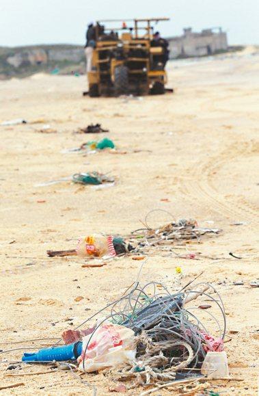 在金門后扁海灘,照片後方的淨灘人士正準備上工,清除眼前的塑膠垃圾。 聯合報系資料...