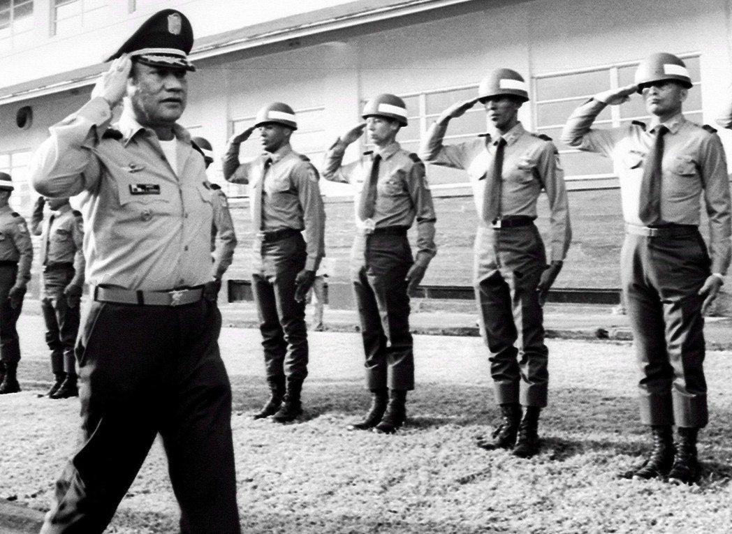 1985年,諾瑞嘉(左)對舉手敬禮的官兵回禮。 (歐新社)