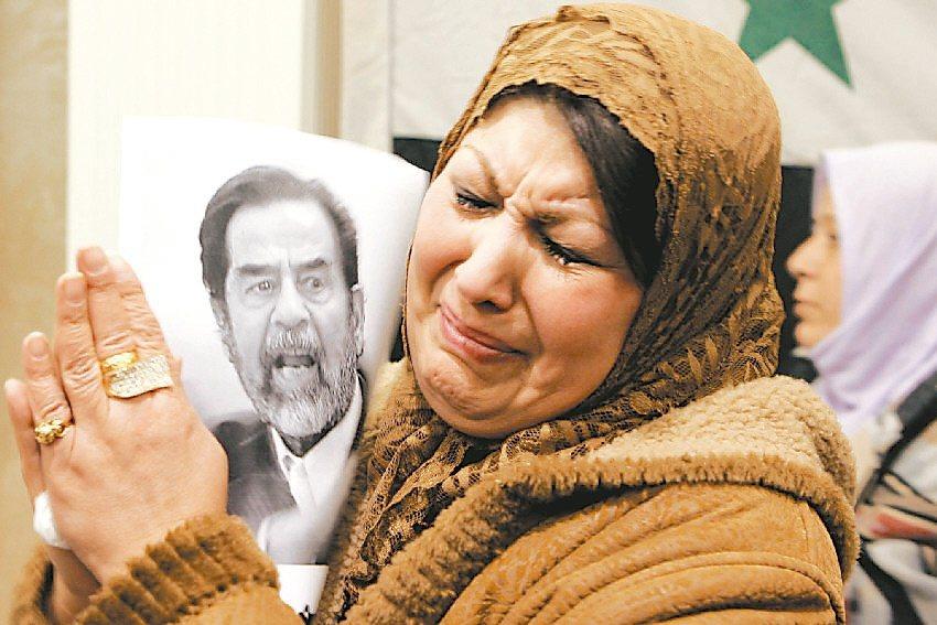 海珊處刑過程被偷拍流傳,當時引發伊拉克人示威,圖為一名約旦婦女捧著海珊的照片,神...