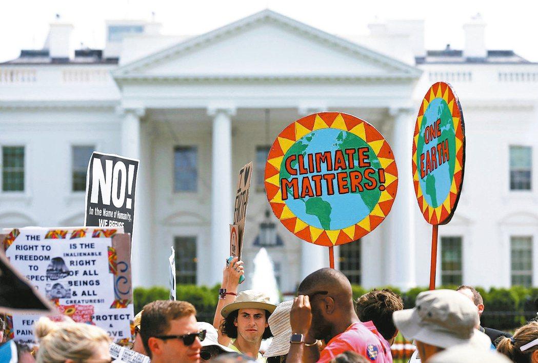 美國總統川普是否退出巴黎氣候協定,即將揭曉。圖為民眾4月底高舉標語在白宮前抗議,...