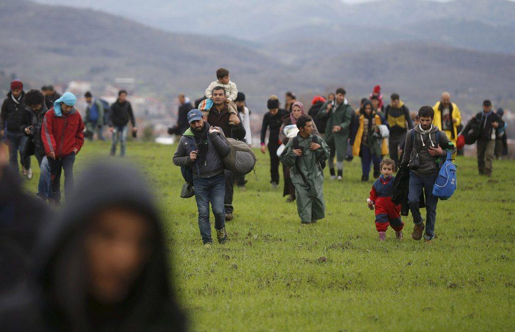 面容疲倦的難民們,他們拖家帶口,風塵僕僕一路向前,用腳步丈量著異鄉的大地。 圖/...